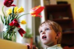 Chłopiec podziwia tyulpami Zdjęcie Stock