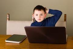 Chłopiec pracuje na pastylce i laptopie Fotografia Royalty Free