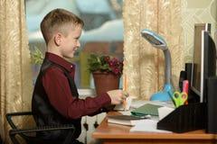 Chłopiec pracuje w jego biurze na osobistym komputerze Pisze dowcipie Obraz Stock