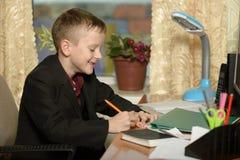 Chłopiec pracuje w jego biurze na osobistym komputerze Pisze l Fotografia Royalty Free