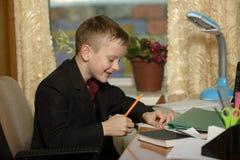 Chłopiec pracuje w jego biurze na osobistym komputerze Pisze l Obraz Royalty Free
