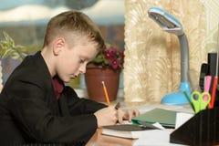 Chłopiec pracuje w jego biurze na osobistym komputerze Pisze l Obrazy Royalty Free