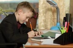 Chłopiec pracuje w jego biurze na osobistym komputerze Pisze l Zdjęcie Royalty Free