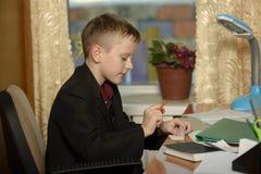 Chłopiec pracuje w jego biurze na osobistym komputerze Siedzi w Obrazy Stock