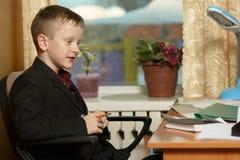 Chłopiec pracuje w jego biurze na osobistym komputerze Siedzi w Zdjęcia Stock