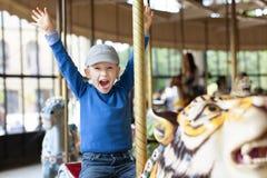 Chłopiec przy carousel Obrazy Stock