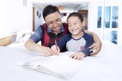 Chłopiec robi pracie domowej z jego ojcem Zdjęcia Royalty Free