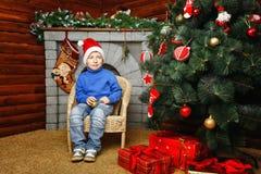 Chłopiec siedzi blisko choinki i prezentów Fotografia Royalty Free