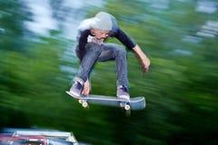 Chłopiec skacze na deskorolka w skatepark Zdjęcia Stock