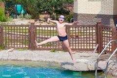Chłopiec skacze w basenie Fotografia Stock