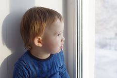 Chłopiec spojrzenia z okno w zimie Zdjęcie Royalty Free