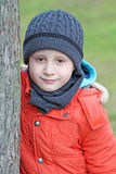 Chłopiec stojaki za drzewem Fotografia Stock