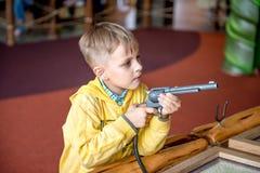 Chłopiec strzelanina koltem w parku rozrywki Obraz Stock