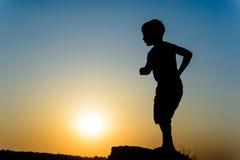 Chłopiec sylwetkowa przeciw zmierzchowi Zdjęcia Royalty Free