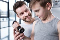 Chłopiec szkolenie z dumbbell wraz z trenerem Obrazy Stock