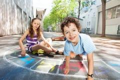 Chłopiec sztuka na drogowym robi hopscotch i remis Obrazy Stock
