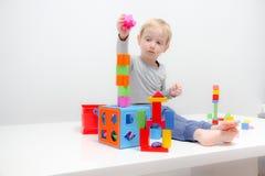 Chłopiec trzy lat siedzi na sztukach i stole Fotografia Royalty Free