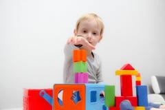 Chłopiec trzy lat siedzi na sztukach i stole Zdjęcia Royalty Free