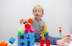 Chłopiec trzy lat siedzi na sztukach i stole Zdjęcie Royalty Free