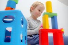 Chłopiec trzy lat siedzi na sztukach i stole Obrazy Stock