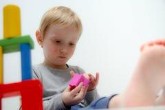 Chłopiec trzy lat siedzi na sztukach i stole Fotografia Stock