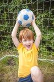 Chłopiec trzyma up futbol Zdjęcia Stock