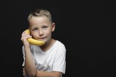Chłopiec use banan jako telefon obraz royalty free