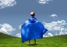 Chłopiec w bohater kostiumowej pozyci na obszarach trawiastych przeciw niebu w tle Obrazy Royalty Free
