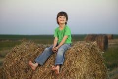 Chłopiec w haystack w polu Obrazy Royalty Free