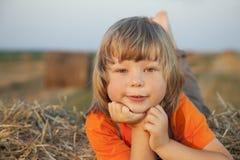 Chłopiec w haystack w polu Zdjęcia Royalty Free