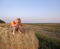 Chłopiec w haystack w polu Zdjęcie Royalty Free