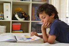 Chłopiec w jego izbowych dopatrywanie komiczkach Obraz Royalty Free
