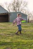 Chłopiec w kraju rzuca frisbee Obrazy Royalty Free