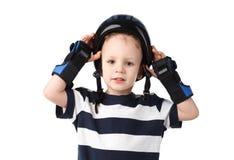 Chłopiec w nadgarstku ochronnych ochraniaczach stawia protec lub usuwa Obraz Royalty Free