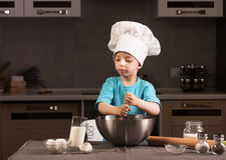 Chłopiec w szefa kuchni kapeluszowym kucharstwie w kuchni Fotografia Stock