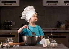 Chłopiec w szefa kuchni kapeluszowym kucharstwie w kuchni Obrazy Royalty Free