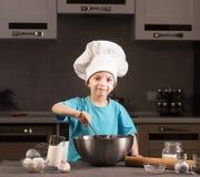Chłopiec w szefa kuchni kapeluszowym kucharstwie w kuchni Zdjęcie Royalty Free