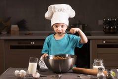 Chłopiec w szefa kuchni kapeluszowym kucharstwie w kuchni Fotografia Royalty Free