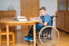 Chłopiec w wózku inwalidzkim robi pracie domowej Zdjęcia Stock