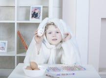 Chłopiec w Wielkanocnego królika kostiumu maluje jajka Zdjęcie Stock