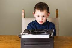 Chłopiec writing na starym maszyna do pisania zdjęcia stock