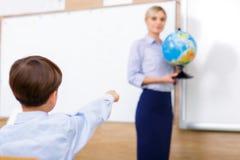 Chłopiec wskazuje przy kula ziemska modelem Zdjęcie Stock
