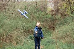 Ch?opiec wszczyna b??kitnego samolot w niebo w zwartym lesie obraz royalty free