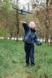 Ch?opiec wszczyna b??kitnego samolot w niebo w zwartym lesie fotografia stock