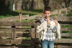 Chłopiec z barankiem na gospodarstwie rolnym Zdjęcie Stock