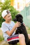Chłopiec z czarnym pudlem Zdjęcia Stock