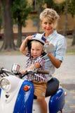 Chłopiec z jego macierzystym obsiadaniem na hulajnoga Zdjęcie Royalty Free