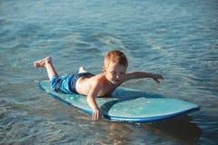Chłopiec z kipieli deski uczenie surfingiem Obrazy Stock