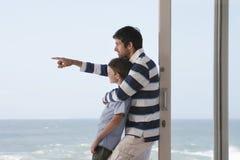 Chłopiec Z ojcem Wskazuje Out morze Zdjęcie Stock