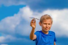 Chłopiec z papieru samolotem przeciw niebieskiemu niebu Fotografia Stock